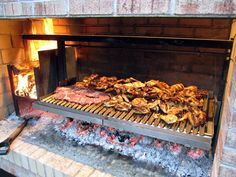 Cooking with a parrilla grill uses wood or charcoal in a brasero to cook meat asado style with a rotating grill crank wheel, an Argentine grill in your backyard. Outdoor Kitchen Patio, Outdoor Kitchen Countertops, Outdoor Oven, Outdoor Cooking, Outdoor Barbeque, Fire Grill, Bbq Grill, Parilla Grill, Parrilla Interior