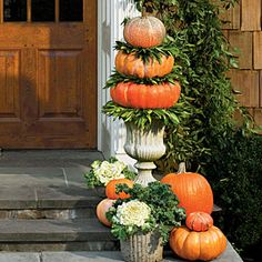 50 Fabulous Fall Decorating Ideas | Pumpkin Topiary | SouthernLiving.com - Vertical displays make a big statement at the front door. Tucking in cool-weather edibles such as ornamental flowering cabbages, kale, and bay leaves adds a distinctive twist. To create topiaries, sandwich bay wreaths between pumpkins stacked in concrete urns, and top with a small pumpkin.
