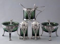 This is not contemporary - image from a gallery of vintage and/or antique objects. KATE HARRIS for HUTTON & SONS  An Art Nouveau silver cruet set with matching spoons.