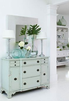 Dress up blank wall space with a dresser, table lamps, great mirror, and a playful mix of demijohns.