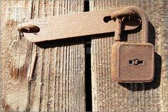 Old rustic padlock on wooden doors