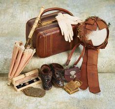 Including a firm-sided leather valise with gold pencil stripe and bail handle,fine woven bonnet with brown silk faille ribbons,feathers and trim,bone-handled parasol,leather purse,gloves,gilt album,and a pair of brown leather ankle boots, French, circa 1870.