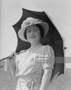 The Queen Mother (1900 - 2002) poses with an umbrella at Windsor Castle, England…
