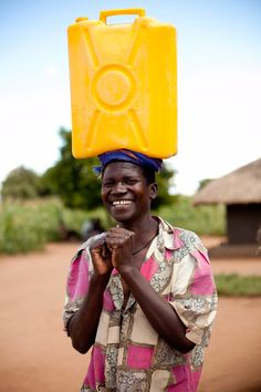 Smiles from a man in rural Uganda, balancing a Jerry can of water on his head. (photo: Esther Havens)