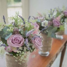 Short sumptuous table arrangements wrapped in rustic hessian with country flowers