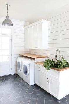 Black herringbone slate floors with white-laundry-room