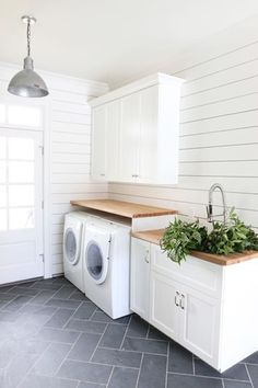 Black herringbone slate floors with white-laundry-room