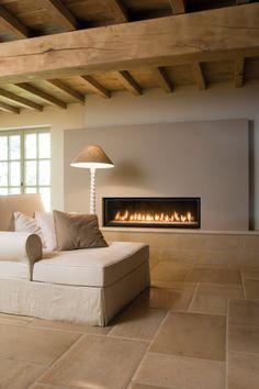 Landelijke kamer in lichte natuurtinten en een natuurstenen vloer van Kersbergen die doorloopt in de muur waardoor de kamer groter lijkt.