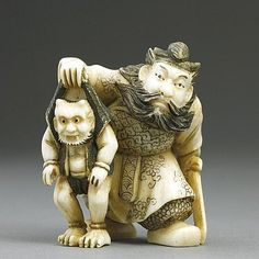ANTIQUE JAPANESE CARVED IVORY NETSUKE  of a Samurai holding a sword while he grabs a horned creature by the collar.