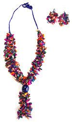 Blue Multicolor Long Melon Seed Set, Colombia - Necklace and earring set. Necklace features multicolored dried melon seeds hand-woven onto blue cord, with a bright blue acai seed. Slip-knot closure allows for length to be adjusted slightly. Earrings match necklace with large cluster of seeds. Handmade by a cooperative of women in Colombia working together to sustainably harvest, dry and hand-color indigenous seeds to create unique jewelry.