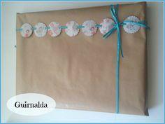 Foto de Regalo envuelto en papel craft con guirnalda hecha con troquel de galleta y cinta de tela