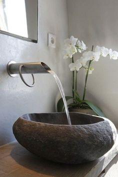 Effetto naturale in bagno con i lavabi in pietra naturale e i miscelatori a canna