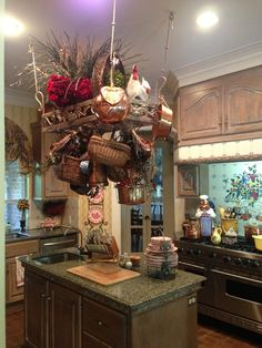 Great small kitchen with a awesome pot rack.  You can tell this is a working kitchen! Also the tiled splash behind the stove top is bright and cheerful.. Truly a Country French Kitchen:  Designed by Tara Morgan Designs