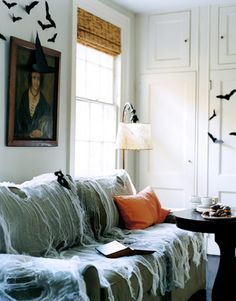 Easy Halloween party decor ideas: Drape a sofa in white gauze or cheesecloth to resemble spider webs, hang an antique portrait on the wall, and affix paper bats around the room.