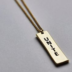 Reversible UNITE Collection Bar Necklace in Gold Brass // Shop this unique necklace to support a mission of unity and acceptance at https://www.exohdesigns.com/collections/unite-collection/products/unite-bar-necklace-brass-2?variant=11510116225