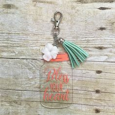 """3 inch tall clear acrylic keychain is embellished with coral vinyl that says """"Bless Your Heart."""" Accented with a mint green tassel and white flower charm."""