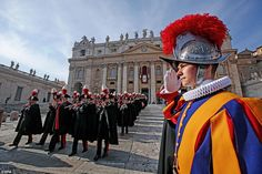 A Swiss guard (right) salutes as an Italian Carabinieri music band marches off at the end of the Christmas Day message