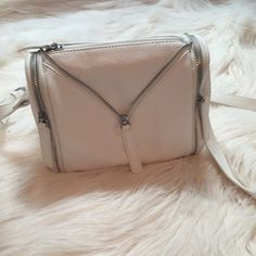 White crossbody bag White Crossbody bag with zipper detailing. Has three zip compartments, the larger middle one, and two small side zip pockets. From forever 21, I used this bag twice, and there is small dirt spots on the bottom. Forever 21 Bags Crossbody Bags