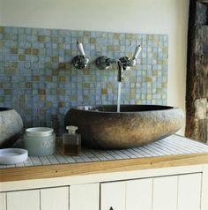 Połączenie różnych materiałów w tej łazience dało miły dla oka efekt. Nieregularna forma kamiennej umywalki na tle błękitnej szklanej mozaiki jest bardzo wyrazista. Blat nad rustykalną szafką wyłożono kamienną mozaiką i wykończono estetycznie drewnianą listwą.