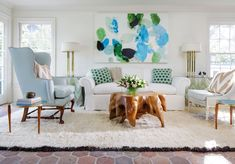 The formal living room is home to a Wickersham sofa from George Cameron Nash, a Stuart Mathews sculpture from 20cdesign, a custom Lucite chair, a brass table from Nick Brock Antiques, a coffee table from Cain Modern, and a rug from The Rug Company.