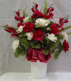 Hoop basket with red, pink, and cream silk roses, red Gladiolas, and green accents.  Basked is weighted at the bottom to keep it upright.