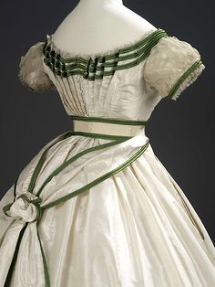 Worth Girl's dress, Silk and sheer cotton,1867. ROM Museum. Simply rendered, this gown is perfect in many ways: the green ribbon almost tracing the details of the gown. The fan front is very beautiful and unique.