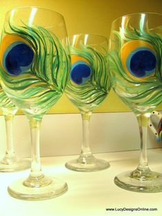 <3 Pin it and win a trip to New York, Barcelona, Berlin, Rome or London. - hand painted peacock feather on dollar store wine glass | Tutorial from Lucy Designs Online.