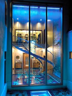 Million Dollar Foyer Acqua Liana's spectacular entryway, seen here through windows at the rear of the home, features a sweeping glass staircase and specially designed water walls.
