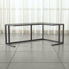 Shop Pilsen Graphite Glass Corner Desk.   By positioning the shorter side to the right or left, the desk adjusts to different room layouts, providing additional, space-savvy workspace.  Arrange multiples in a U shape for even more workspace surface area.
