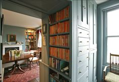 View into Teal Sitting room through wall of books