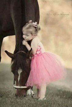 Precious little girl in a pink tutu hugging a sweet horse.