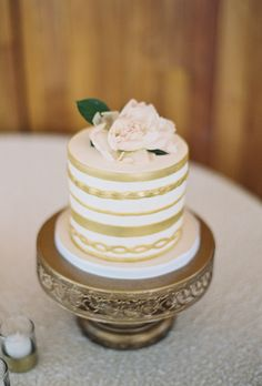 Brides.com: 29 Glam Metallic Wedding Cakes. A single-tier gold-stripped wedding cake with fresh flower topper, from Hey There, Cupcake.