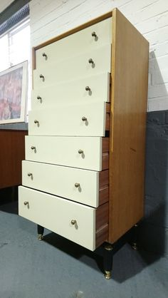 Elegant seven drawer tallboy chest in oak with Chinese White finish to the drawers made by G-Plan in the 1950s. This stylish piece features the classic 1950s G-Plan ebonised leg structure, brass drawer handles and original paint to the drawer fronts.