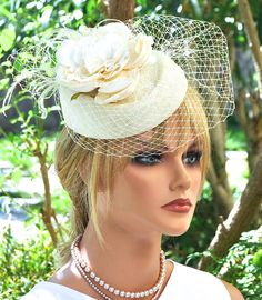 AWARD MILLINERY DESIGN I made this delicate ivory fascinator hat in my millinery studio in the Hollywood Hills. Its adorned with ivory veiling, a silk and lace flower and finished off with a few floaty feathers. Very feminine. One-of-a-Kind The hat attaches with a millinery elastic