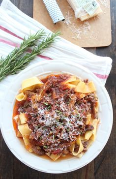 Slow Cooked Beef Ragu  1 large onion (sliced) 4 garlic cloves 2 tbsp fresh rosemary (chopped) 2 lb beef chuck roast 1 tsp kosher salt 1 tsp black pepper 2 cups beef broth ¼ cup red wine 1 can (6 oz) tomato paste 1 can (15 oz) diced tomatoes 12 ounces pappardelle pasta or polenta ½ cup Parmesan cheese (grated)