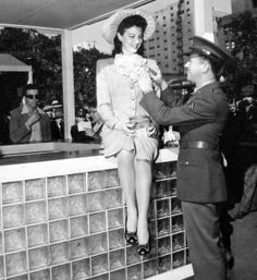 Corporal Leon Hayes pins a bouquet of war savings stamps on Ava Gardner as she appeared at Victory House to autograph stamp albums.