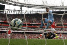 Manchester City's Sergio Aguero (R) scores a goal against Arsenal during their English Premier League soccer match at the Emirates stadium in London September 13, 2014. REUTERS/Eddie Keogh