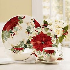 Holiday Grace Dinnerware – The Paragon. Set on a white table cloth with a Poinsetta center piece & Christmas is served