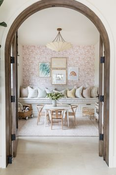 An arched doorway framed in natural wood leads into a pretty pink playroom. Pattered wallpaper, room for toys and activities, and a cozy bench for reading. Home Decor Inspiration, House, Soft Furniture, Interior, Home, Playroom, Interior Design, Decorating Your Home, Pink Playroom