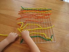 Weaving pipe cleaners in a cooling rack ~ Fine Motor Skills Activity