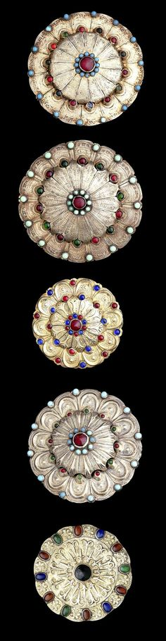 Central Asia | Five Turkman silver gilt ornaments; each of lobed circular form, decorated in repoussé with vegetal designs, inlaid with coloured glass | late 19th to early 20th century | Est. £ 1'500 / 2'000 ~ (Jun '14)