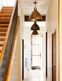 Hanging gold light fixtures and wood staircase
