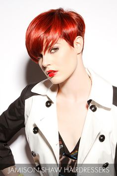A luminous hair color puts the cherry on top of this dynamic short cut that features a heavy side-swept bang and shapely sides.