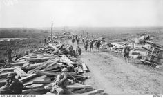 A view of the supply dumps along the Menin Road, in the Ypres sector, showing the traffic moving out from the direction of Ypres towards the forward zone. At left background is a battery of 6 inch guns, in line with Birr Cross Roads behind the trucks. The vital importance of this road explains the appalling artillery fire to which it was subjected. 20 September, 1917.