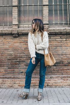 Sara of Collage Vintage is cozy in a cable knit sweater, cuffed jeans, snake print boots, and a bucket bag