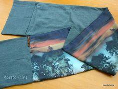 """Abrazo, gevoerde sjaal met 2 zakken   Deze dubbelzijdige sjaal is gemaakt voor de palliatieve zorg van Sutfene en heet Abrazo (""""omarming"""" in het Spaans). De zachte katoenen joggingstof valt soepel. De andere zijde is van viscose met een print van een avondlucht en bomen. De grijze kant heeft 2 zakdelen aan het uiteinde. Hierin blijven handen warm. Ook kun je er dierbare spulletjes in stoppen of juist een streelzacht sjaaltje."""
