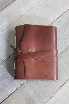 This is a unique, handbound leather journal ready to record your thoughts, dreams, sketches, lists, or anything you can think of. This journal was carefully made with a wrap-around leather closure which will keep your writing safe and secure (a pen will fit nicely inside as well).