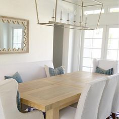 Dining Room. Neutral dining room Coastal white and blue dining room with Darlana Linear Chandelier, white slipcovered chairs and denim pillows by JP Cajuste Pillows. Table is made by Sarri #DiningRoom Rita Chan Interiors.
