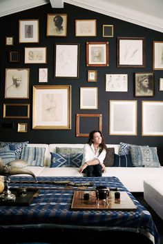 """""""Who says you can't wear black with blue? It's the play between bone black walls and deep indigo textiles that builds intrigue in our family den,"""" says Smith. A white sofa highlights that tension, while warm woods """"help dark walls feel none too slick,"""" she says."""