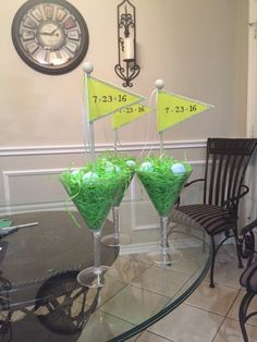 "Golf Bay Table Centerpieces - FRONT Plastic Martini Glasses.  Hot glue flower foam cone in center to stick flag in to.  Fill with bags of ""Easter"" grass and several golf balls on top.  We used felt to make the flags, dowels, and dowel toppers that we glued in place."